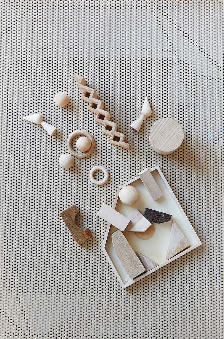 Rings, balls, blocks and remnants of pale wood on perforated panel