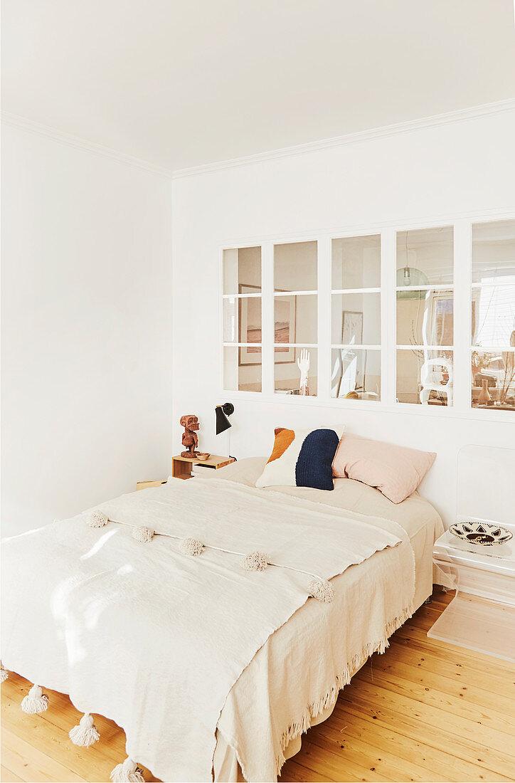 Blanket with tassels on bed below internal bedroom window