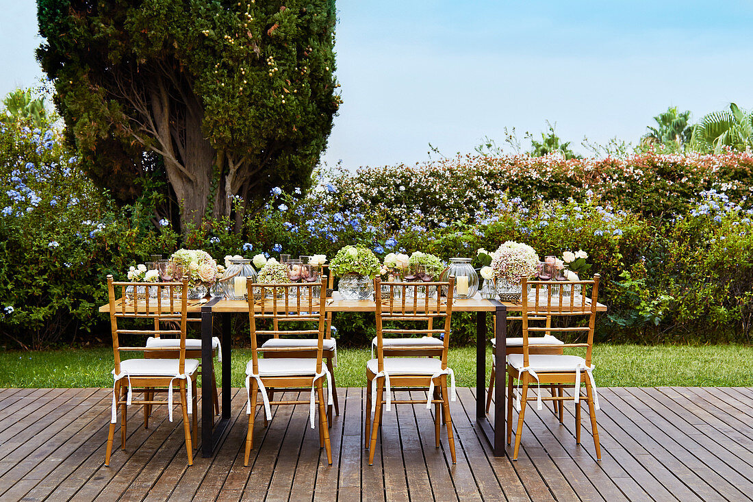 Table festively set with hydrangeas and candle lanterns on wooden deck
