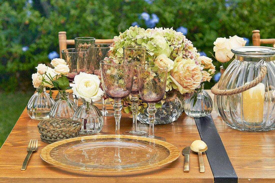 Table festively set with charger plates, hydrangeas, roses and candle lanterns