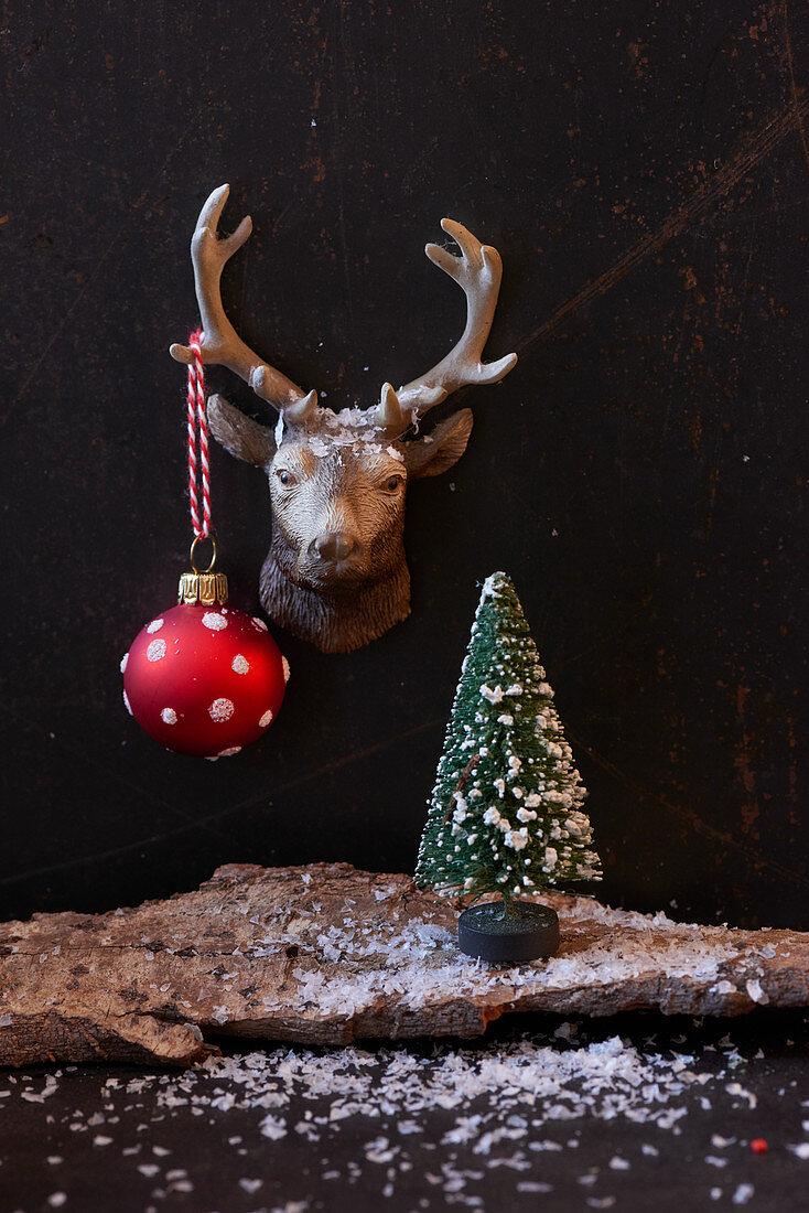 Weihnachtsdekoration mit Rentierkopf, Baumkugel und Tannenbäumchen