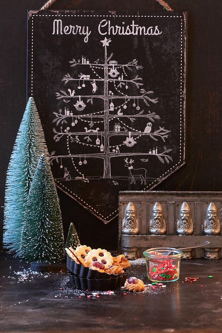 Weihnachtsbaum-Tafel, im Vordergrund Tannenbäumchen, Plätzchen und Vintage Backform