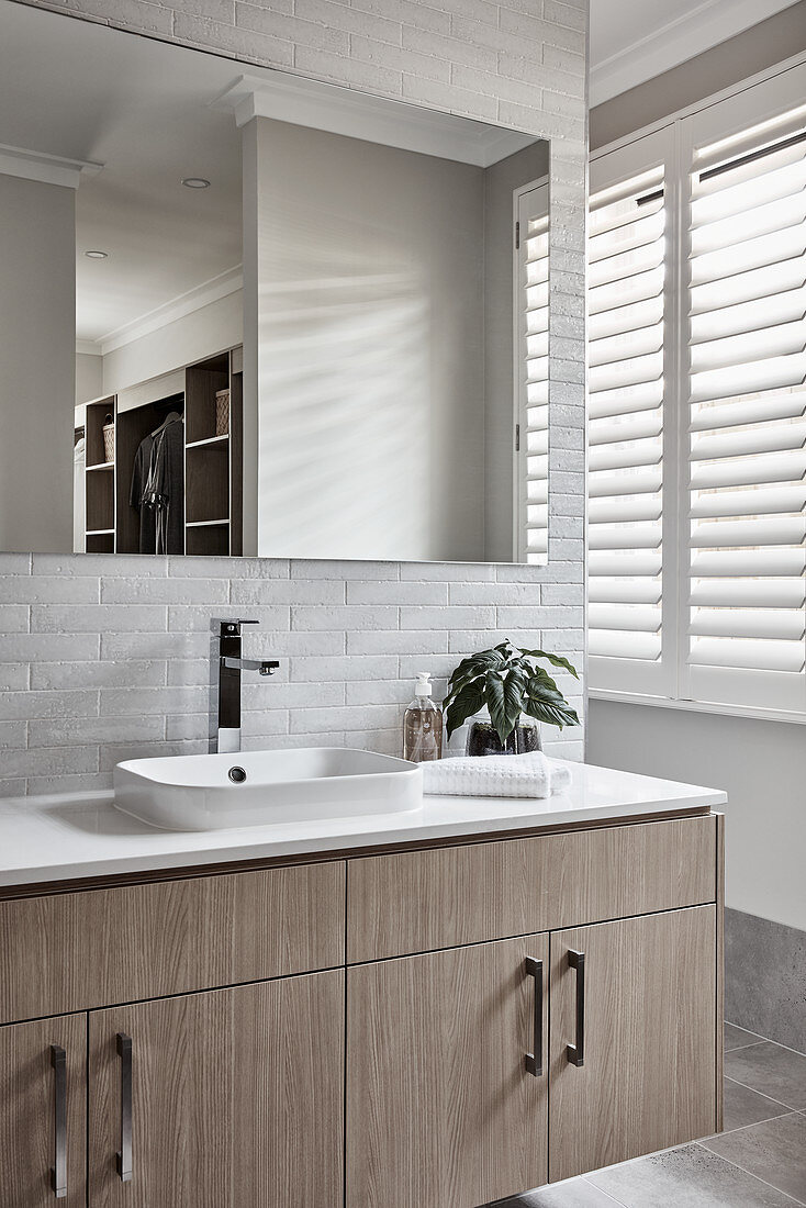 Washstand with countertop sink and mirror on white brick wall