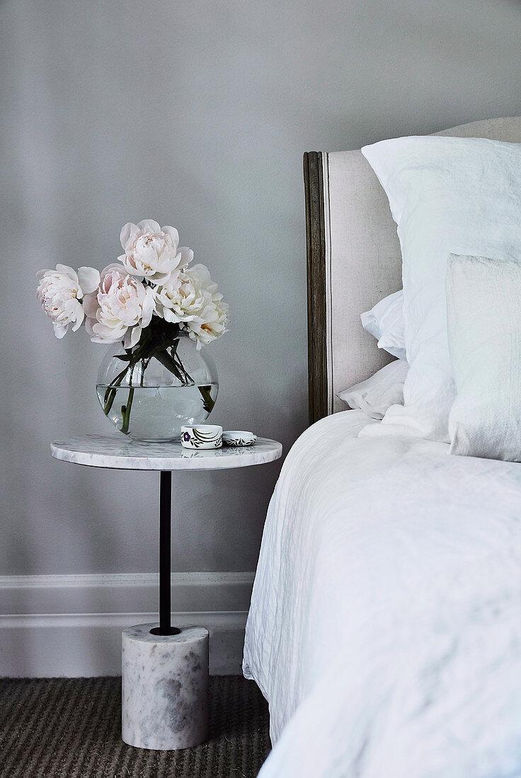 Pfingstrosen auf dem Nachttisch aus Marmor im Schlafzimmer in Grau
