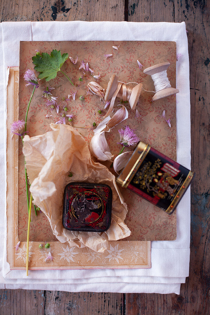 Vintage-style arrangement of garlic cloves, wooden reels and tin