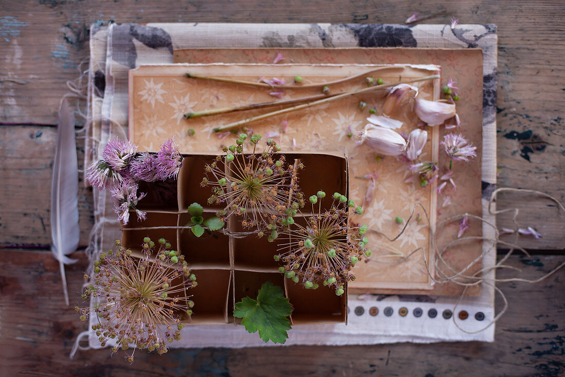 Vintage-style arrangement with garlic cloves, flowers and cardboard box