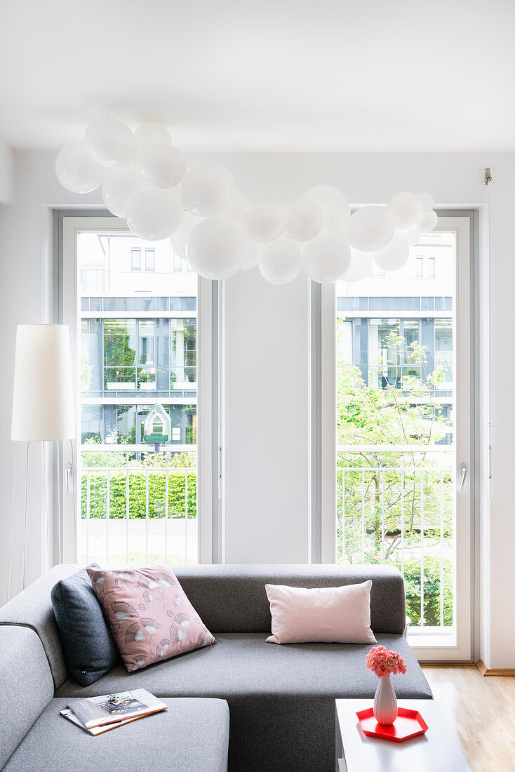 Cloud of white balloons above sofa in living room