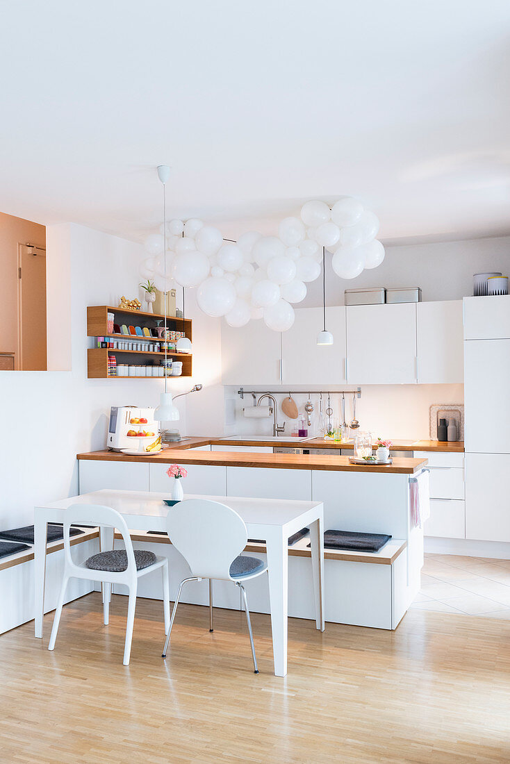Cloud of white balloons above island counter in bright, open-plan kitchen