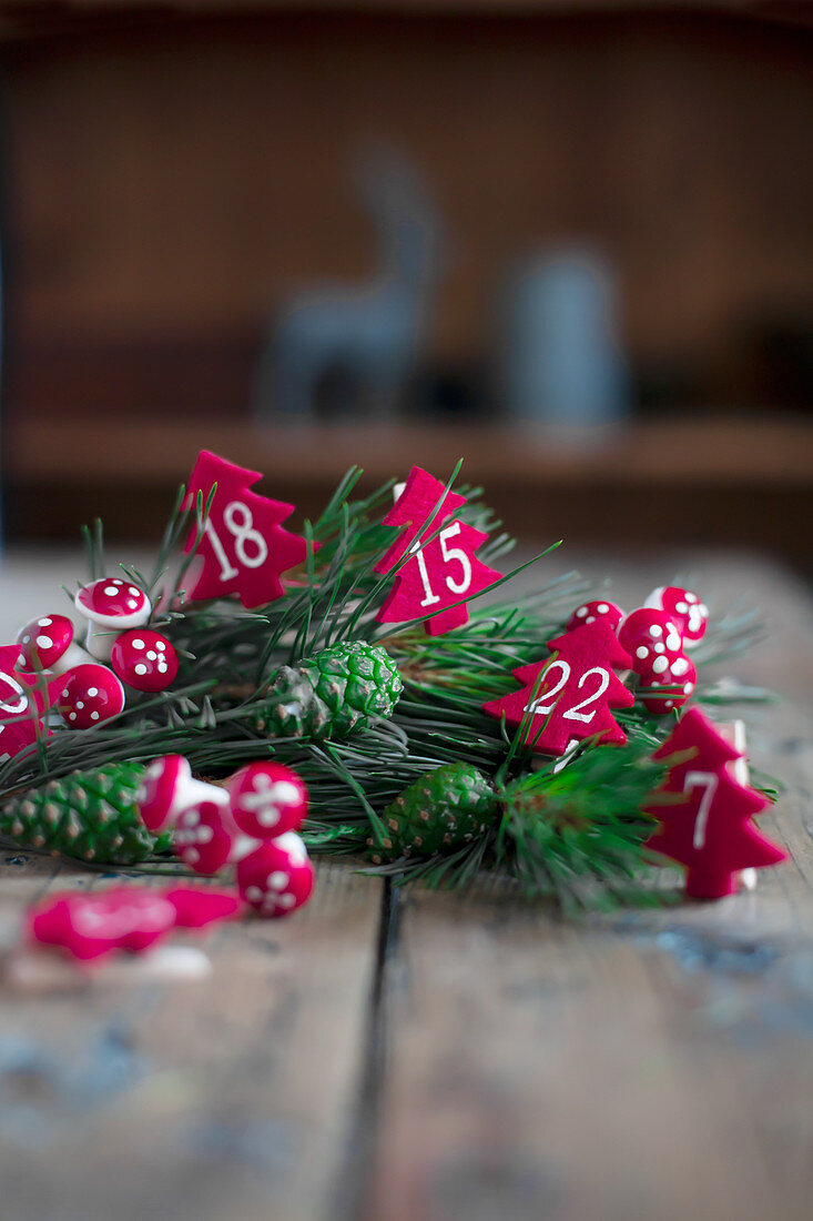 Numbered Christmas trees made from red felt and conifer twigs