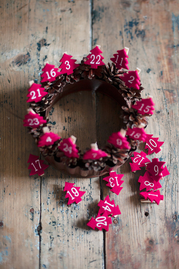 Wreath of pine cones with numbered, red felt Christmas trees
