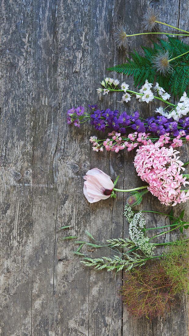 Blüten und Samenstände auf Holzbrett