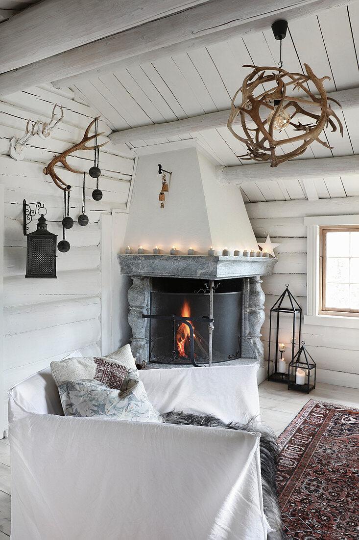Open corner fireplace in rustic living room of log cabin