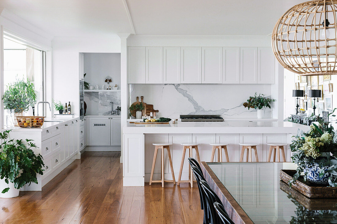 White kitchen with counter and dining area, splash protection in marble look