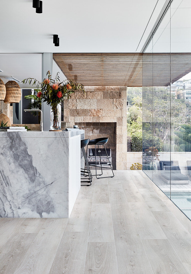 Marble island counter in open-plan kitchen with wooden floor and glass wall