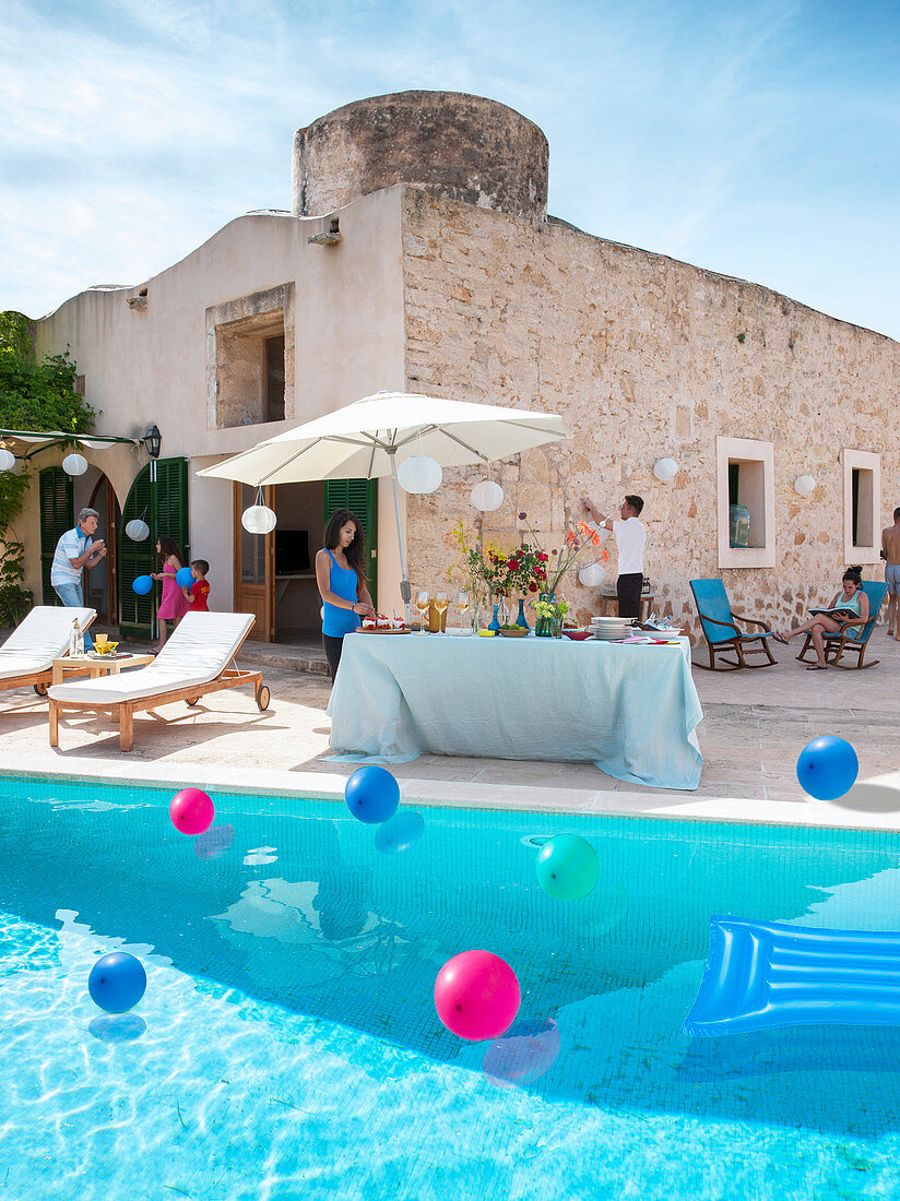 Party buffet under parasol next to colourful balloons floating in sunny swimming pool