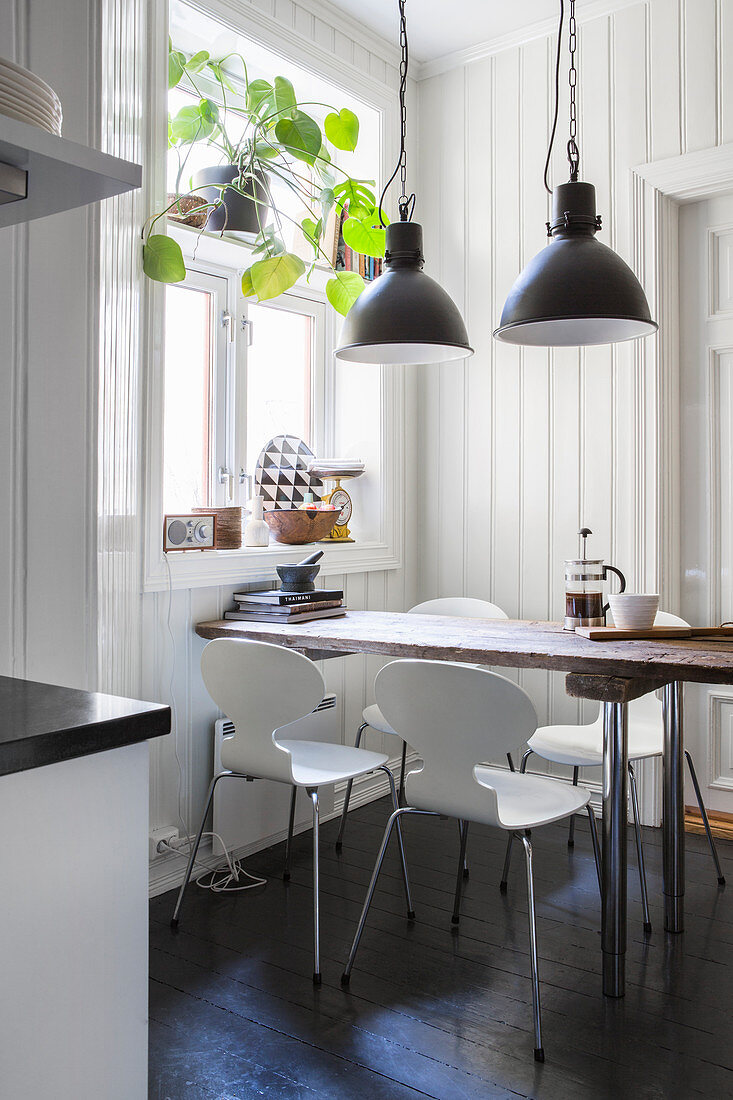 Designer chairs around wooden table in rustic kitchen-dining room