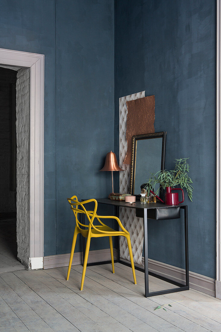 Yellow chair at dressing table against blue walls in period apartment
