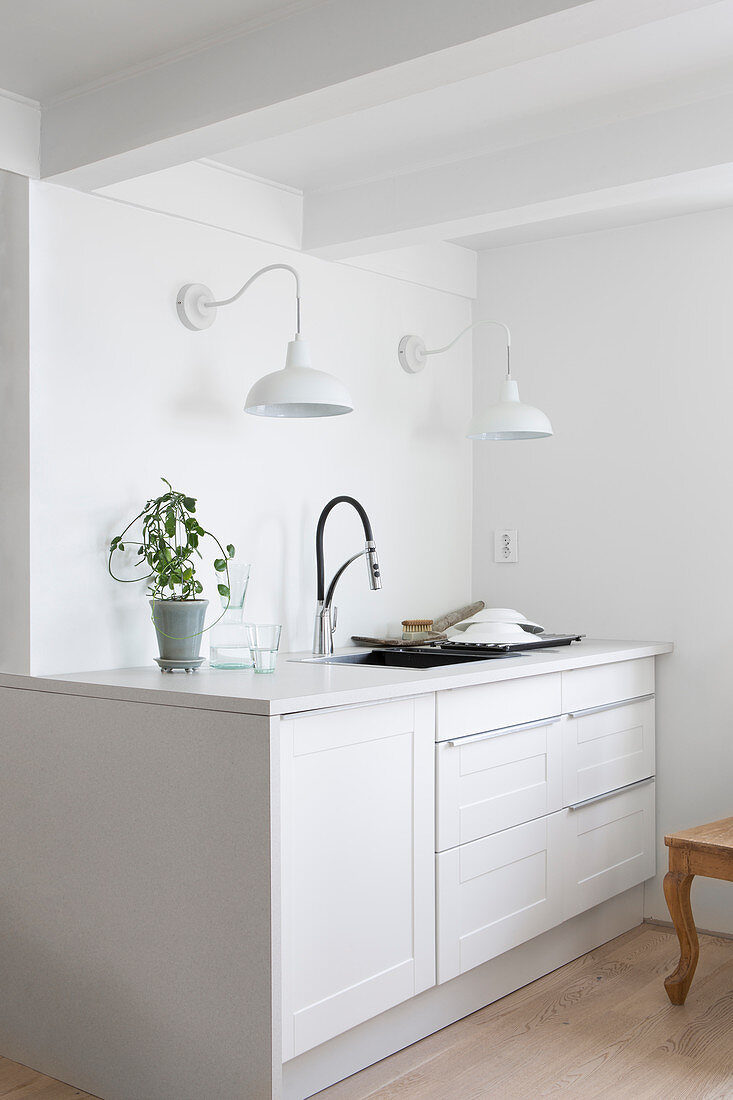 Two wall lamps above white kitchen counter in country-house style