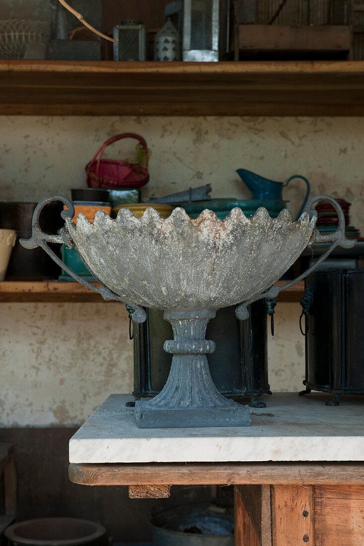 Antikes Pflanzgefäss auf Tisch in Gartenpavillon