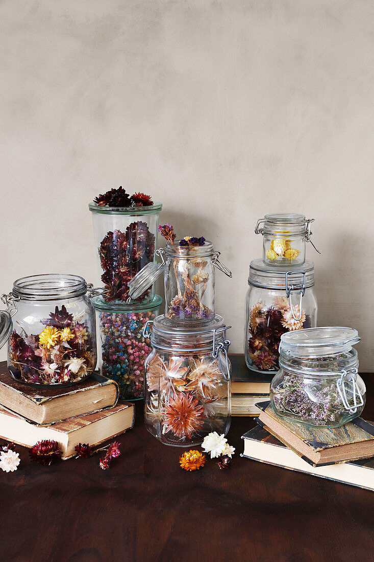 Dried flowers in preserving jars on old books