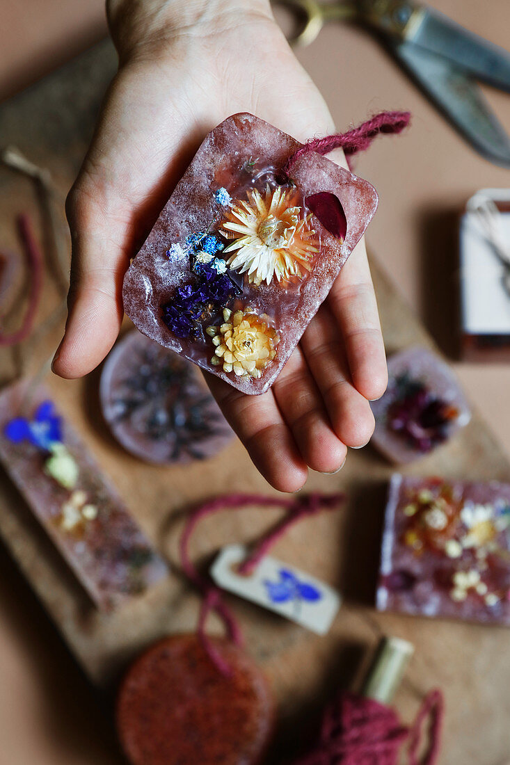 Hand holding handmade scented wax with dried flowers