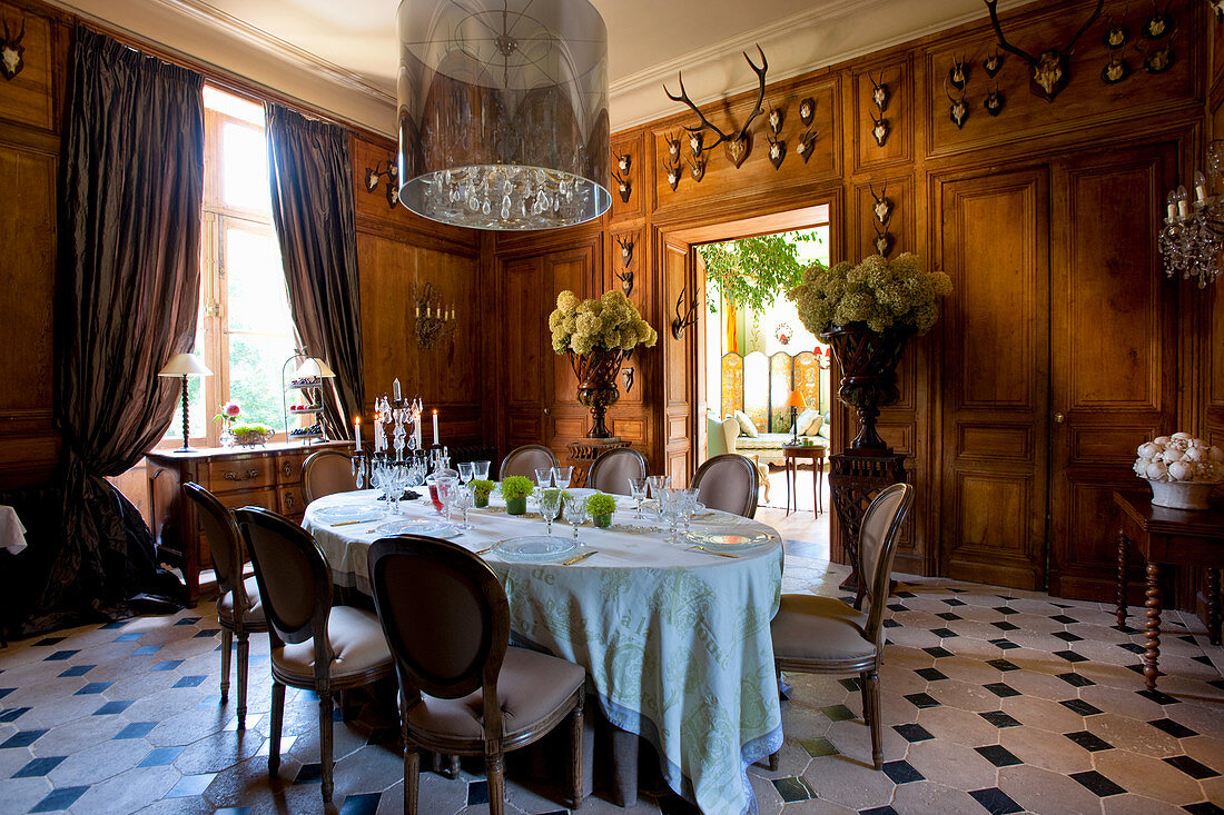 Wood-panelled walls decorated with hunting trophies in stylish dining room
