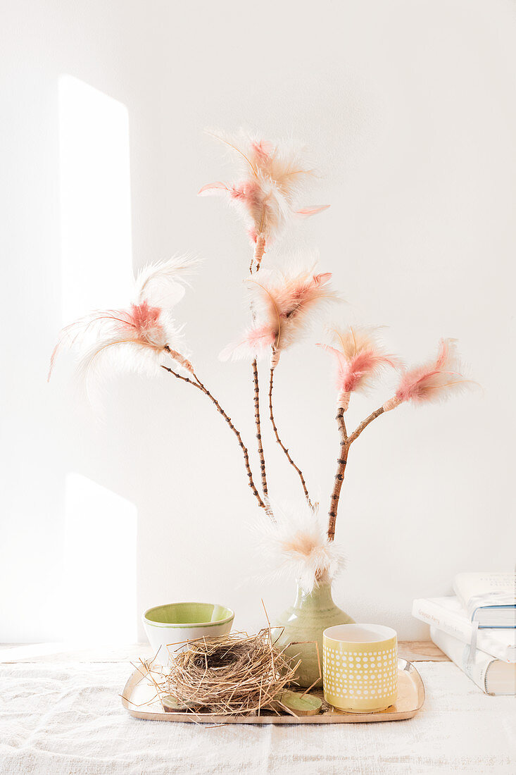 Pastel spring arrangement of feathers on twigs, straw nest and ceramics