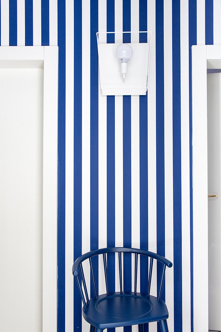 Dark blue chair against blue-and-white striped wallpaper