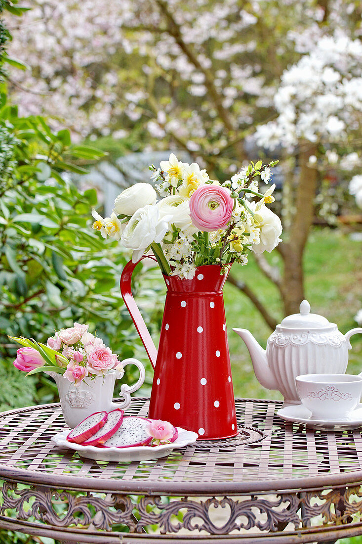 Spring bouquet with ranunculus, daffodils and blossom branches in a tin can, mini-bouquet of rose blossoms, and tulips in a creamer pitcher