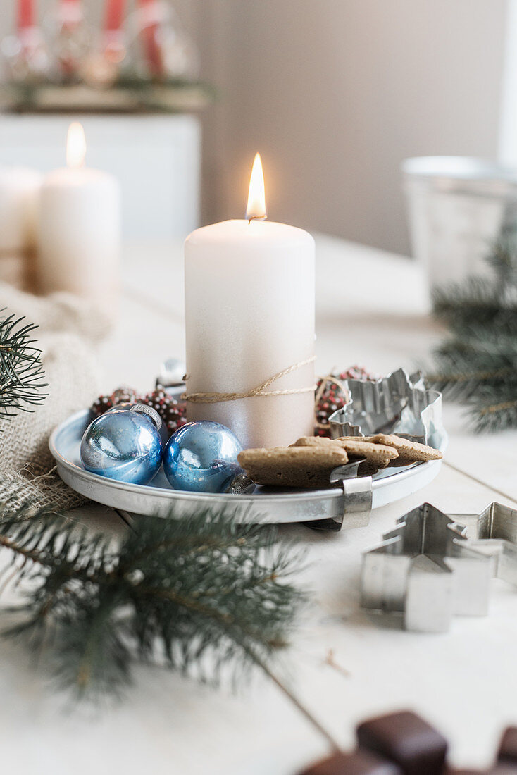 Lit candle on metal plate, pastry cutters and blue baubles