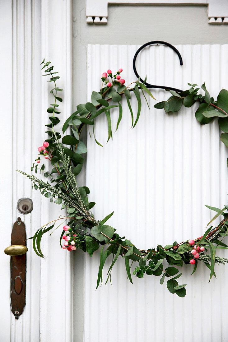 Wintry wreath of eucalyptus and snowberries on door