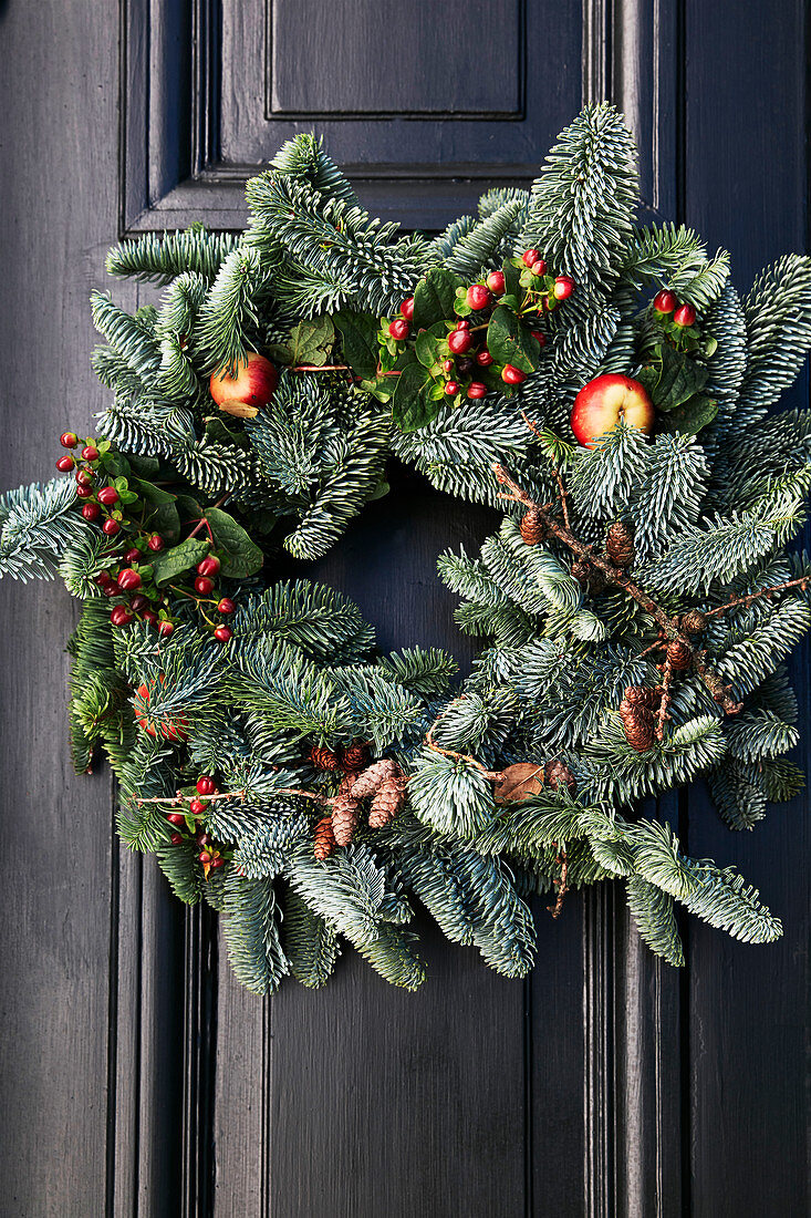 Wintry wreath of fir branches, berries, pine cones and crab apples