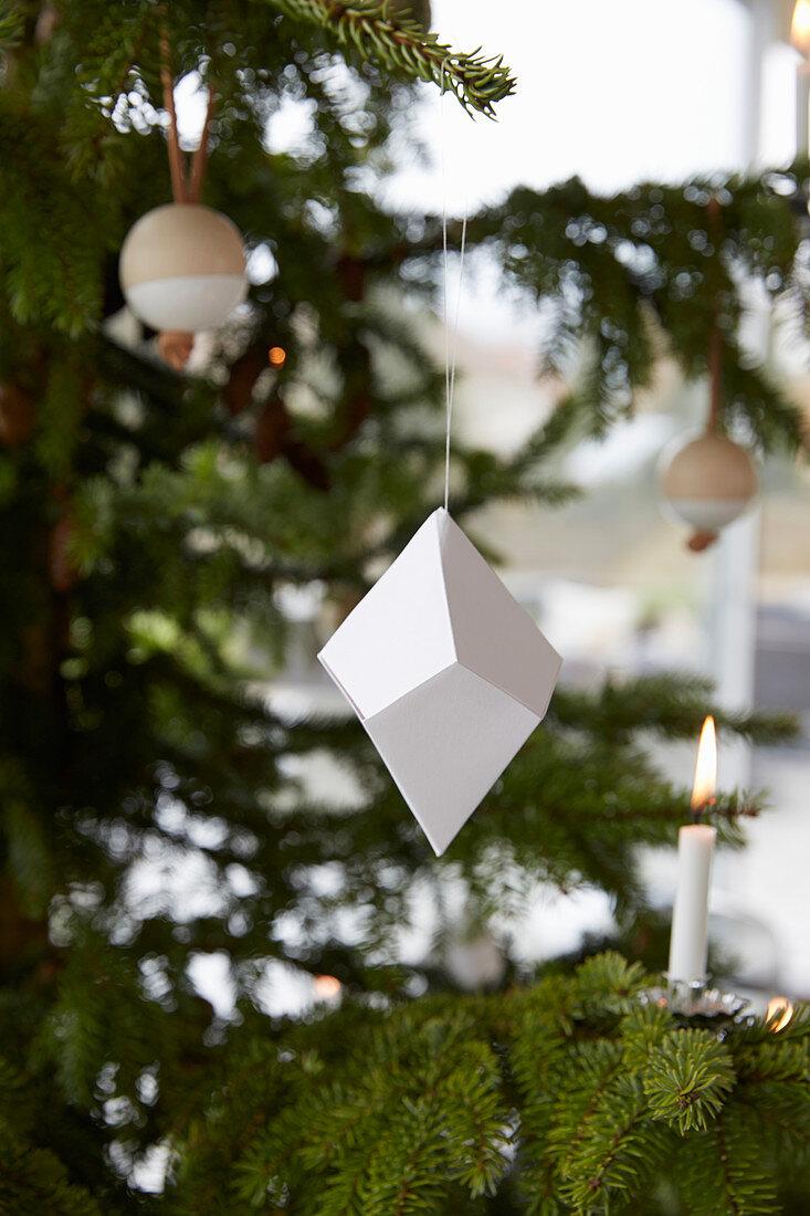 Origami, Kerze und Holzkugel am Weihnachtsbaum