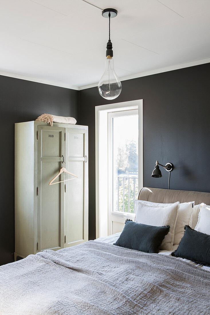 Locker-style wardrobe in bedroom with black walls