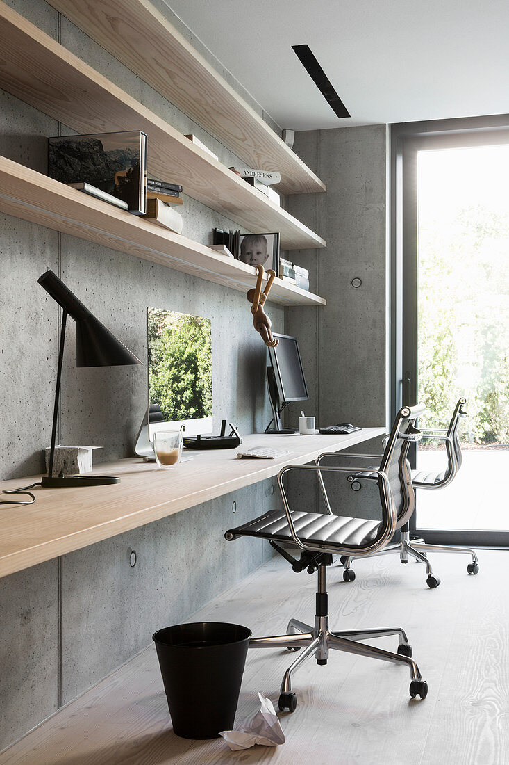 Fitted desk and shelves made from wooden boards on concrete wall
