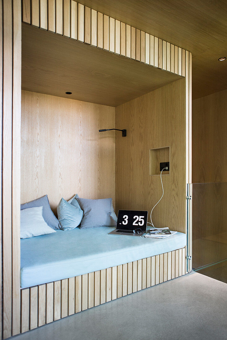 Modern alcove seat with pale wooden panelling in architect-design house