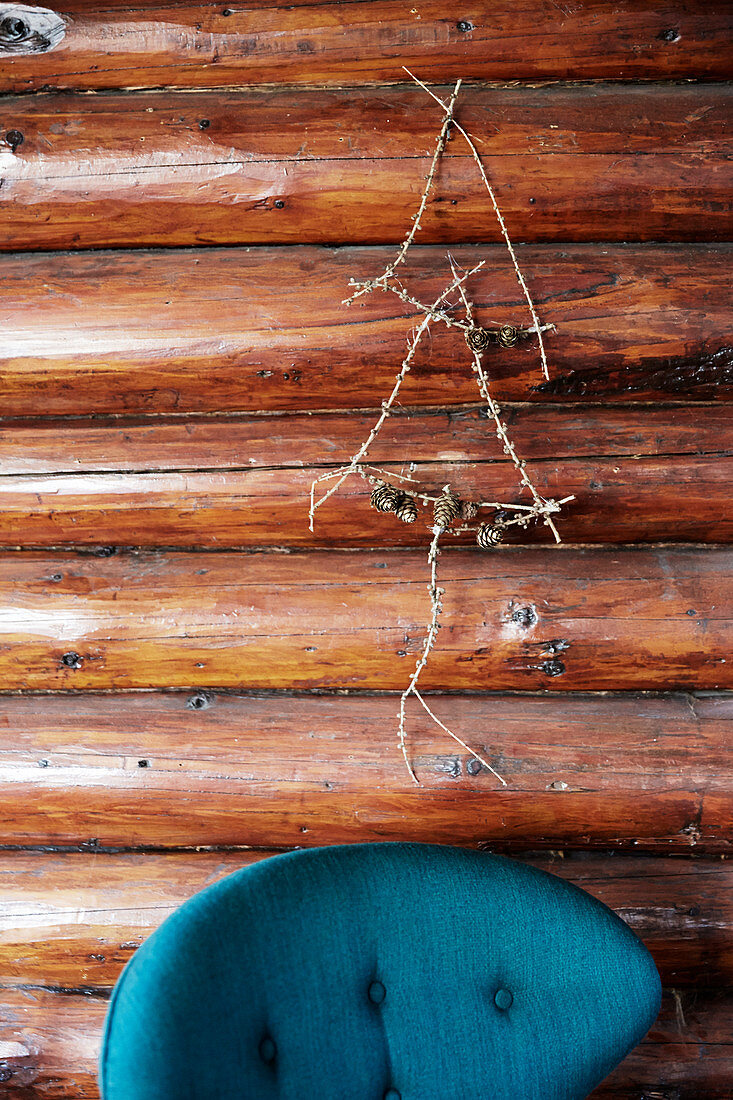 Stylised Christmas tree made from twigs on wooden wall