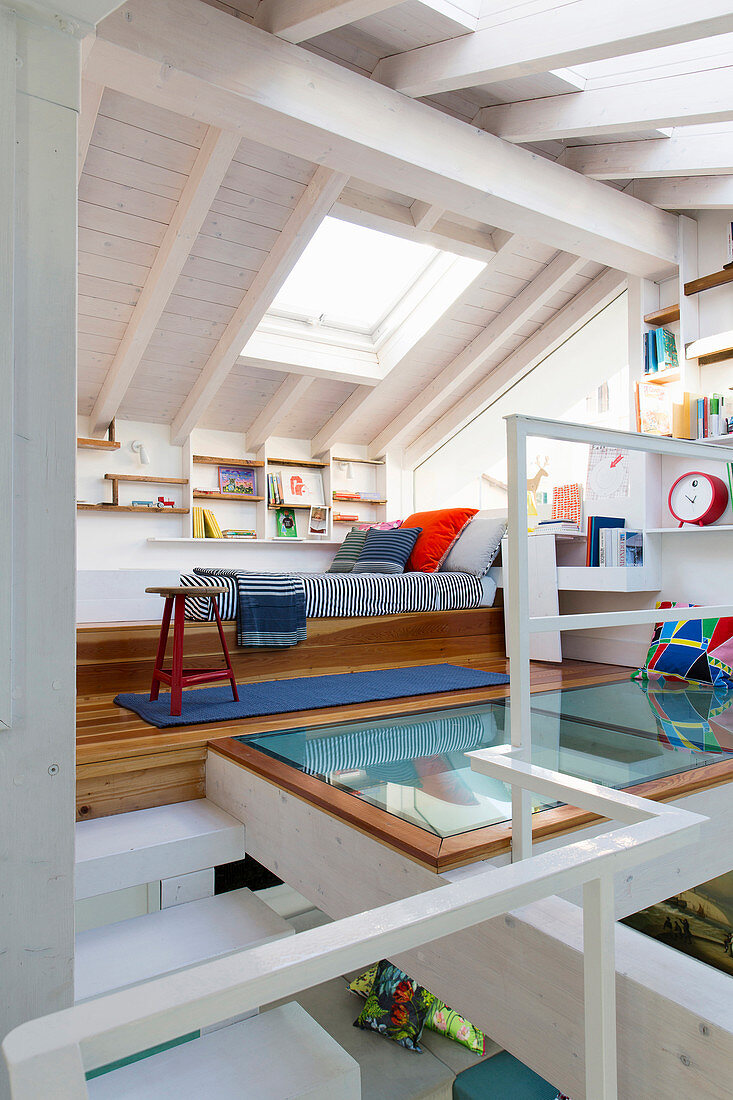 Bed and shelving in teenager's attic bedroom