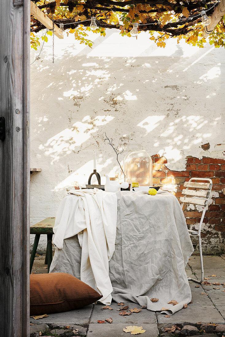 Crumpled layered fabrics on table below pergola