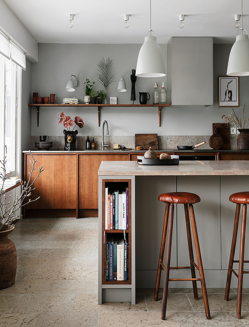 Bar stools at counter in open-plan kitchen in earthy shades