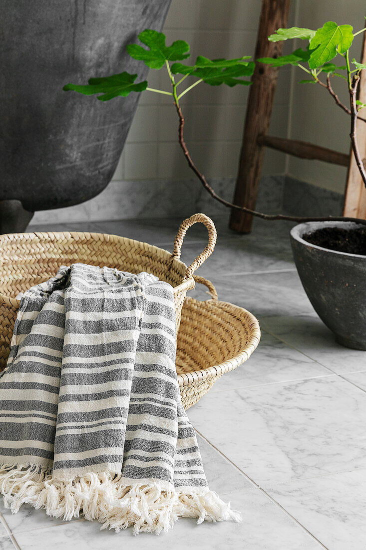 Striped cotton towel in basket next to bathtub