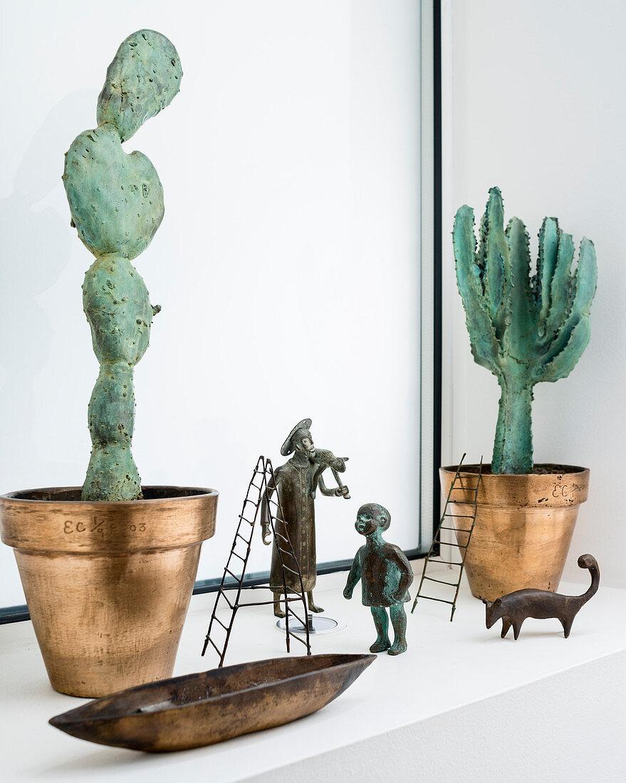 Arrangement of cactus sculptures and bronze figurines