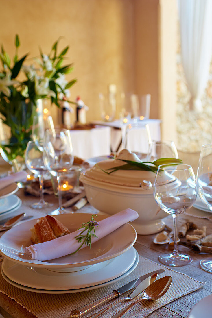Table set in Mediterranean style with white crockery and silver cutlery