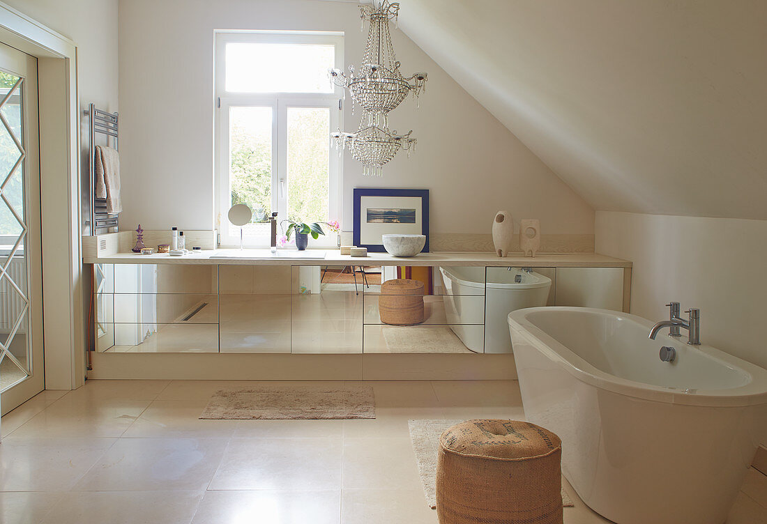 Long, mirrored washstand in large, cream bathroom