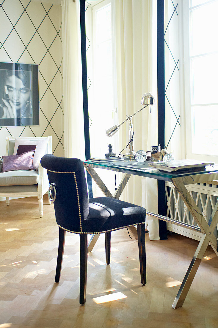 Writing area below window: chair with blue upholstery and glass desk on metal frame
