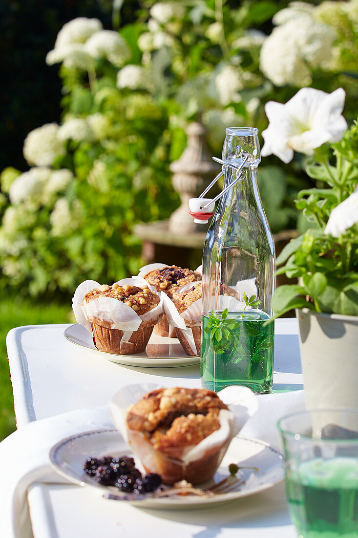 Muffins and swing-top bottle of mint syrup on garden table