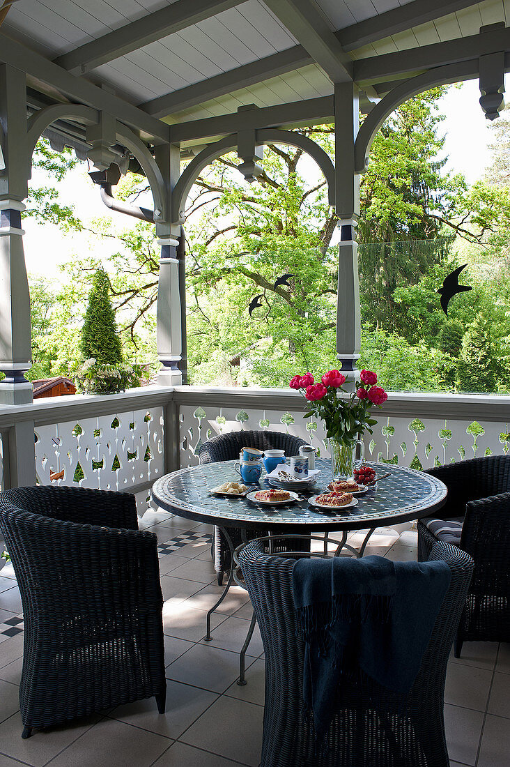 Black wicker chairs around mosaic table on roofed terrace