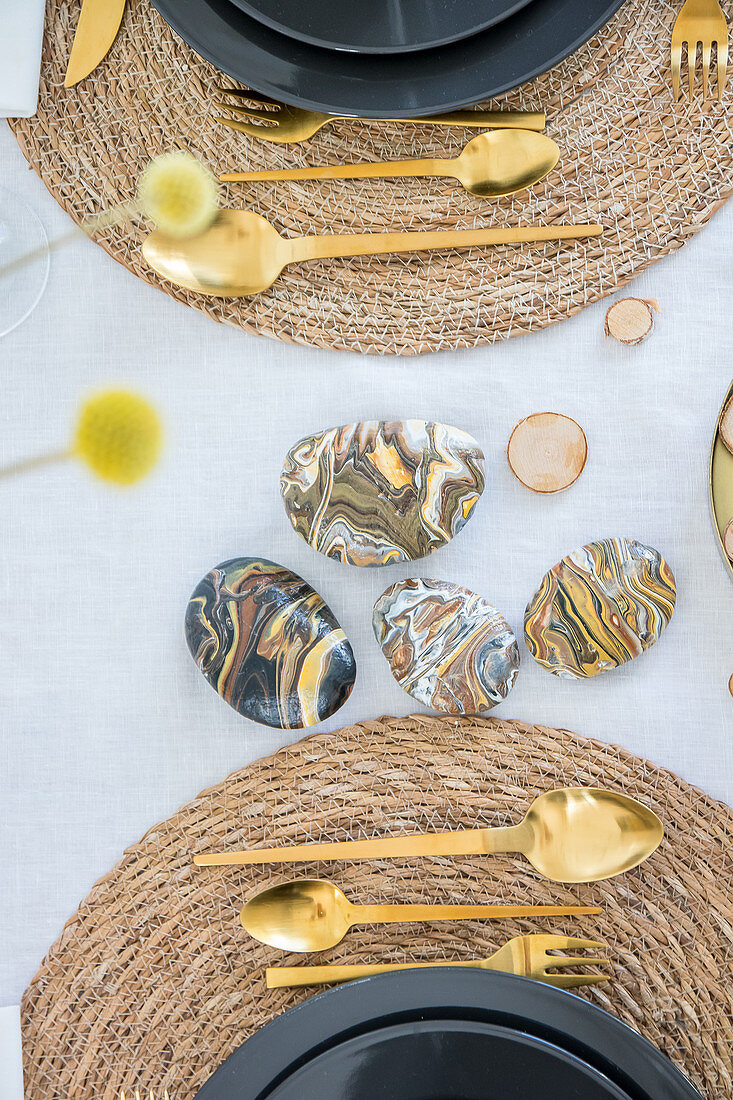 Pebbles painted with marble pour technique in natural colours on set table