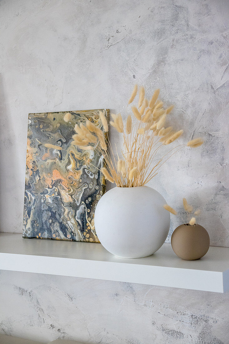 Canvas painted with marble pour technique in natural colours on shelf