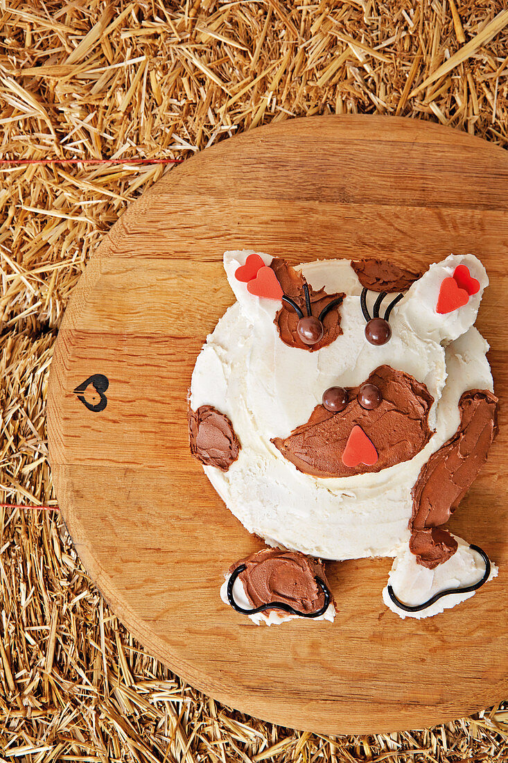 Two-tiered cake with cow's face covered in white and brown buttercream